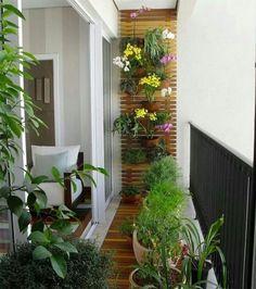 Balcón utilizado como un pequeño jardín con un panel de listones de madera del que cuelgan maceteros con plantas, suculentas y flores. En el piso siguiendo la linea delpanel, un caminito de madera y sobre el más maceteros con plantas.