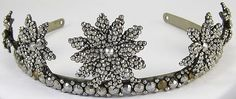 antique Georgian/Victorian era tiara of cut steel in a floral motif. Five sparkling cut steel florets decorate the band on this wonderful tiara. The steels are riveted to a brass band. The brass band is then riveted to a white metal band. The white metal band may be a later addition to the piece. The florettes are densely packed with faceted steels, each having 12 facets.