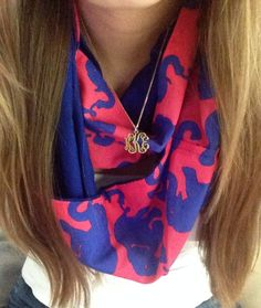 Scarf, long hair, and monogrammed necklace.