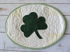 Welcome! You have entered An Angel A Day, Quilts etc... territory.  For your decorating pleasure, I have created a sweet Shamrock candle mat. This quilt has been crafted from 100% quilt shop cottons. The background is a patchwork of various creams and whites. The shamrock is a deep green Moda Marble. You can see a slight marble variation in the fabrics appearance. The shamrock was hand cut and then stitched to the background with a pretty green thread with a raw edge technique. Once you wash…