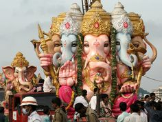 Ganesha is transported on huge cranes by devotees before immersion.