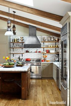 Reclaimed wood on the island, shelves, and beams, all from Heritage Salvage, and raw steel on the brackets and hood — fabricated by Ogletree's — look strong enough to stand up to anything. Wolf range. GE Profile dishwasher. Cabinetry is painted Benjamin Moore's Kingsport Gray. James Baigrie  - HouseBeautiful.com