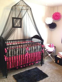 Black and pink Damask bedding in nursery. Hanging pom poms. Black crib canopy netting. Fuzzy black rug. Only pink and green!