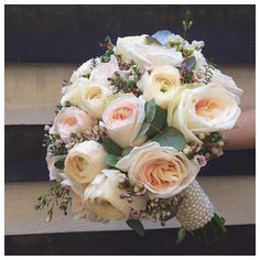 Bridal bouquet with rananculus, garden roses and wax flowers, accented with a pearl handle.