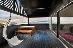 Modern, semi-enclosed balcony space with black wooden deck and hanging white chairs. By Chris Humphreys Photography Ltd