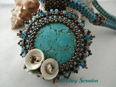 Embroidery necklace.A turquoise cabochon beaded with toho and miyuki seedbeads,swarovski bicones and finished little green shells.The neklace is made