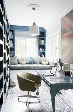 Narrow home office with window bench, modern light fixture, and large British flag art