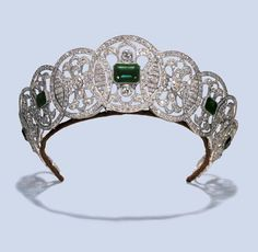 A BELLE EPOQUE DIAMOND TIARA, Designed as thirteen graduated openwork panels, set with old-cut diamonds, five of which are centred with rectangular-cut emerald simulants, circa 1910, 44.5 cm. wide, with French assay marks for platinum