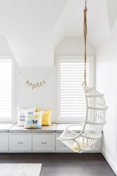 White cottage teen girl's bedroom features a white rattan chair hanging from a rope suspended from the ceiling placed next to a long built in window seat bench lined with platinum gray cushions.