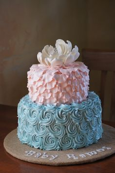 Pink and blue baby shower cake with fondant ruffles and rosettes