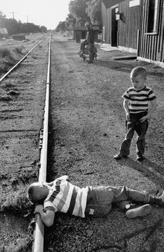 A young boy with his ear to the rail of a railroad track in an attempt to hear  the vibrations of a distant approaching train. Photograph by Walter Sanders. Bradgate, Iowa, USA, August 1950.