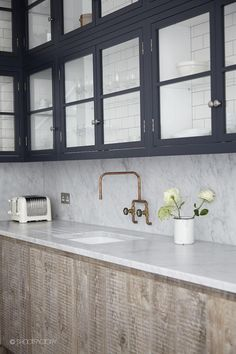 Indigo uppers with glass fronts & subway tile, unlacquered brass fixtures, light woods
