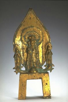 The bodhisattva Avalokiteshvara (Chinese: Guanyin) flanked by attendants  Place of Origin: China  Date: 570  Historical Period: Northern Qi dynasty (550-577)  Object Name: Buddhist shrine  Materials: Gilded bronze  Dimensions: H. 9 1/4 in x W. 4 1/4 in x D. 2 1/4 in, H. 23.5 cm x W. 10.8 cm x D. 5.7 cm