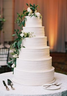 6 tier greenery topped wedding cake: Groom's Suit: Freeds - http://www.stylemepretty.com/portfolio/freeds Floral Design: Breath of Spring - http://www.stylemepretty.com/portfolio/breath-of-spring-2 Wedding Dress: Alon Livne - http://www.stylemepretty.com/portfolio/alon-livne-2   Read More on SMP: http://www.stylemepretty.com/2017/03/20/your-blueprint-for-a-modern-wintry-city-wedding/
