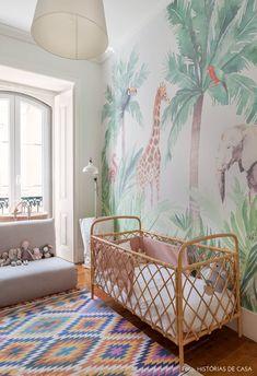Quarto de bebê com papel de parede de floresta tem berço de bambu, luminária de chão branca e poltrona com brinquedos.