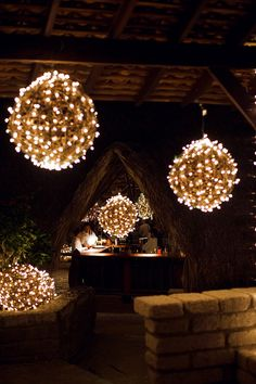 LChristmas lights wrapped around rattan or vine spheres and hung from the ceiling.