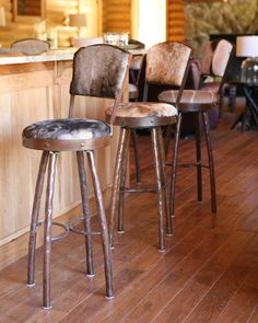 A stool to match any room setting! This bar stool features curved hammered legs with a seat and back covered with custom cowhide and outlined with flat iron. Stools are custom made to fit any height. All finishes are available and come standard covered with brown leather. We also offer the option of providing your own material to cover these seats.
