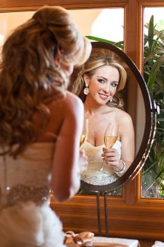 With champagne in hand, the gorgeous bride poses for a wedding photograph.