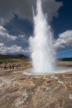 Tourists watching Strokkur Geyser in full eruption, Iceland. It is one of Iceland's most famous geysers, erupting about every 4–8 minutes 15 – 20 m high, sometimes up to 40 m high. Stokkur is a fountain geyser located in the geothermal area beside the Hvítá River in Iceland in the southwest part of the country, east of Reykjavík.