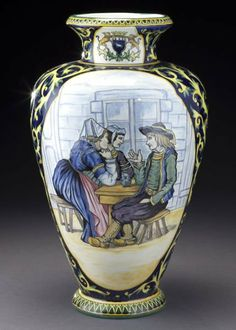 "Henriot Quimper Decor Riche vase, the front reserve featuring two Bretonese ladies and a gentleman at a tavern surmounted by the armorial crest of Quimper, the reverse featuring floral decoration and the crest of Brittany. Marked ""Henriot Quimper"" in blue underglaze. 16""H, Circa - 1930."