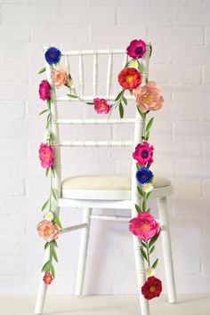 Loving the idea of paper flowers for a fresh take on chair decor