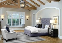 Elegant bedroom features an arched niche filled with a purple velvet bed dressed in purple and black pillows flanked by black mirrored nightstand, Worlds Away Ava Nightstands, facing a small sitting area boasting white roll arm chairs accented with royal blue velvet pillows atop a gray rug.