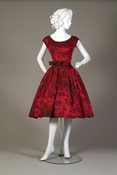 Red and black satin brocade cocktail dress. Dress with wide neck and fitted bodice to hip, dropped waist skirt pleated all around with self petticoat. Small brocade belt to waist with center bow.  American, ca. 1959.  Silverman/Rodgers Collection. KSUM 1983.1.437ab.