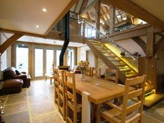 Oak framed lower floor with dining table and central atrium - Carpenter Oak