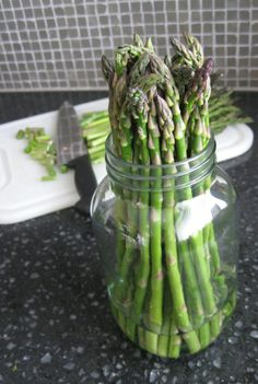 How to Store Fresh Asparagus  Keep asparagus fresh for up to 2 weeks. With a sharp knife, cut off about an inch of the tough bottom ends.   Next, place the asparagus in a quart size jar and fill it with 1 to 2 inches of water.   Place a plastic bag (such as a produce bag) loosely over the jar so it is not touching the asparagus. Pull and twist the bottom of the bag, tucking it under itself to keep it sealed. Place in the refrigerator till needed. Wash when ready to use.