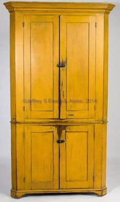 "Price Realized: 6,325.00 SOMERSET CO., PENNSYLVANIA PAINTED PINE CORNER CUPBOARD, two-piece construction, well-executed molded cornice above two paneled doors in upper and lower sections divided by simple waist molding, raised on an applied cut-out bracket base. Mustard-painted surface. Circa 1830-1850. 79"" H, 41"" W, 29"" corner.   Provenance: Collection of the late John and Lil Palmer, Purcellville, VA.  Purchased from Dick Barnes, Old South Antiques, Brownsburg, VA, 1989."