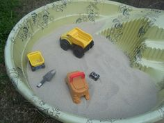 Easy DIY sand box. Only $16 for the sand @ Lowe's (4 bags of play sand). If you don't already have a plastic pool you can find one super cheap for a small basic blue one.
