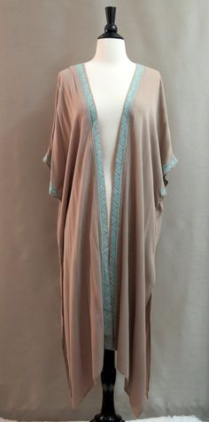 Long taupe embroidered kimono duster features intricate pastel blue embroidered detail that runs down the front and around sleeves. Triangle back key-hole for added style, and high slits on both sides
