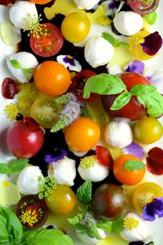 cherry tomatoes paired with cherry-sized mozzarella, fresh herbs, and edible flowers with olive oil and balsamic #capresesalad