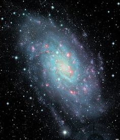 Eight million light years away lies galaxy NGC 2403. Spanning nearly 50,000 light years in diameter, the galaxy displays its incredible spiral arms with hot young stars in blue and glowing star-formation regions in red. (Credit: Canada-France-Hawaii Telescope/Coelum) Tumblr