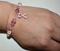 """Breast Cancer Awareness Bracelet full of Swarovski crystals and a metal pink ribbon charm with a lobster clasp.    This bracelet is 8"""" long and should fit Large Size Ladies.  Custom order sizes will be taken.    Bracelet Approximation Size Chart:  6-7 Years: 6""""  8-12 Yeas: 7""""  Ladies Small: 7""""  Ladies Medium: 7.5""""  Ladies Large:  8""""    If you special order a bracelet you can refer to this size chart or measure your wrist and send me the size.  If you measure your own wrist, please remember…"""