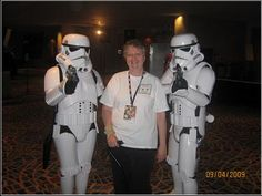 Kayelle Allen with stormtroopers. 2009  These two had been posing with folks by having them kneel and then holding their guns on them. When it was my turn, they saw my cane (I had vertigo that year) and wrist brace (I'd sprained it a week before DC) so they instantly posed as if they were my protectors instead. Very cool!