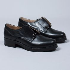 Elia B.  Women's Black Cecil Round Toe Shoe: Black cecil round toe shoe. A simple, unfussy and versatile design from Elia B. It is crafted in black leather and has an elastic opening. The open cut-out blucher style adds a cool androgynous vibe to any look.