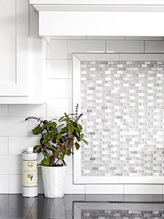 Kitchen Backsplash Ideas: Tile Backsplash Mother-of-pearl tiles above the range add luster and light to the plain white subway tiles. The small tiles help to break up the large expanse of wall and add a fresh look to the kitchen. Kitchen Stove, Kitchen Redo, Kitchen Tiles, Kitchen Colors, Kitchen White, Design Kitchen, Kitchen Cabinets, Glass Backsplash Kitchen, Kitchen Facelift