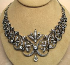 A diamond tiara necklace, unfortunately off its frame, circa 1885. Featuring sixteen scroll and foliate motifs either side of a central laurel leaf spray with large circular diamond and pear-shaped drop diamond.