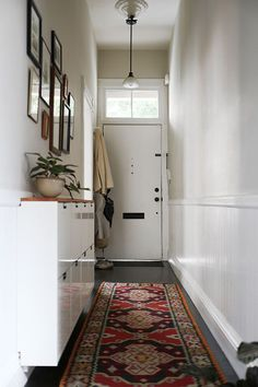 Narrow hallway with white shelfes, an Oriental rug and a white door. Great entryway!