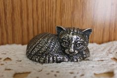 """Reed and Barton Silver Plated Sleepy Kitten   Cute little silver plated kitten ready to go to sleep. The music box plays """"Brahms Lullaby"""". The music box sounds a little tinny and plays the melody fast, but it is in very good condition. I left some patina on the kitten as I thought it looked nice that way.  The kitten measures 3 inches in length and 2 inches wide"""