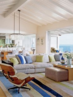 The vaulted, beamed ceiling in this Laguna Beach living room give it a wide-open feel. Natural fiber rugs and cozy plush sectionals help to contrast and give weight to the room's sizeable dimensions. (Photo: Lisa Romerein)