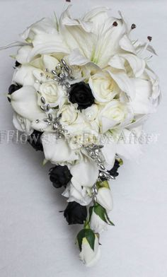 Courtney A modern beauty with a twist. Features real touch white Casablanca lilies, and silk tiger lilies on one side and trailing down the other are classic white roses, black bud roses, real touch mini tulips, real touch calla lilies and scattered silver branch bead clusters with diamantes for a little added glamour. Measures approx 26cm x 45cm Bouquet handle finished and bound with white satin ribbon and silver studs.  ***CONTACT MARIA ON 0439 810 982 for more details.
