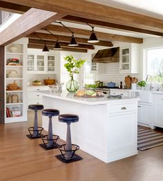 This new kitchen has a historic feel with white walls and an island next to aged-looking wooden beams. Adding some edge to the clean, white space are four zinc-and-black leather barstools.