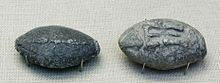 """Lead sling bullets, ca. 100 g with a winged thunderbolt engraved on one side and the inscription """"Take that"""" (ΔΕΞΑΙ) on the other side. Athens, 4th century BC."""