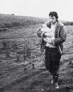 Paul, with baby Mary in his arms, walking across his Scotland farm, circa 1969.