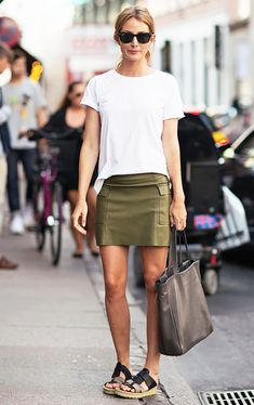 A white t-shirt is paired with an olive green miniskirt, sandals, Ray-Ban sunglasses, and a gray leather tote bag
