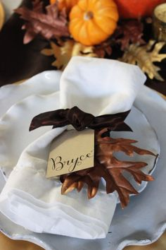 Thanksgiving place setting with metallic leaves, craft paper place card and chocolate brown ribbon.
