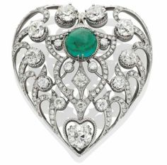 EMERALD AND DIAMOND BROOCH Heart-shaped, perforated, with diamonds old size and size 8/8 and decorated in the center with a cabochon emerald, platinum setting and white gold, gross weight: 35.75 gr, ca. 1950.