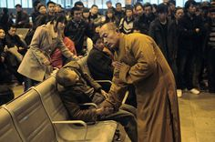 A monk prays for an elderly man who had died suddenly while waiting for a train in Shanxi Taiyuan, China.